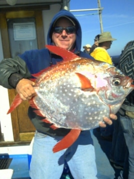 "Shannon Hunter of Newport holds an opah caught last summer on the charter vessel ""Misty."" Opah is normally found in Hawaiian waters."