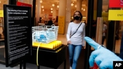 Face masks in a basket at a shop entrance as a woman wearing a face mask to protect herself from COVID-19 leaves in London, Friday, July 24, 2020.