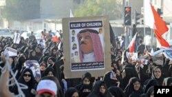 Người biểu tình chống chính phủ ở Bahrain cầm hình của vua Bahrain trong khi dự đám tang của một người biểu tình