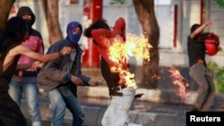 An Indonesian student protester runs after he caught fire while throwing a molotov cocktail towards police during a protest against the new president's decision to hike fuel prices this week in Makassar, South Sulawesi Province, Nov. 19, 2014. (REUTERS/Yusuf Ahmad)