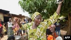 Une des femmes de la communauté Baoulé fait des gestes en préparant de la nourriture lors des célébrations dans le village d'Assounvoue, en Côte d'Ivoire, le 1er avril 2018.