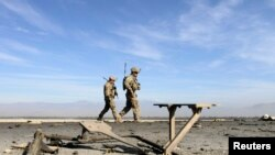 FILE - U.S. troops inspect at the site of a suicide attack on the outskirts of Jalalabad, Nov. 13, 2014.