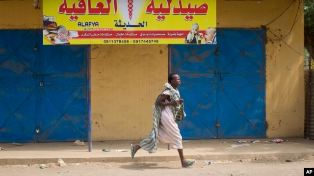 A young woman runs through the street as gunshots ring out a few streets over, in Malakal, Upper Nile State, in South Sudan on Jan. 21, 2014. A ceasefire agreement signed two days later has been repeatedly violated.