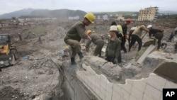 지난 16일 북한 노동자들이 최근 홍수 피해를 입은 함경북도 온성에서 무너진 건물 잔해를 치우고 있다.