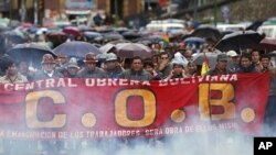 Members of Bolivia's Central Workers union march to protest rising food costs in La Paz; the smoke is from small packages of dynamite set off by the protesters, Feb. 18, 2011