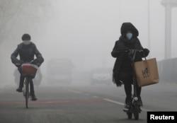 중국 베이징 거리에서 시민들이 자욱한 스모그 속에 자전거를 타고 있다.