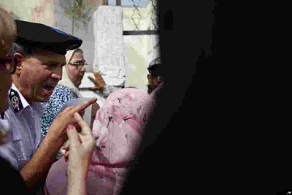 Cảnh sát hướng dẫn đám đông cử tri tại một lối vào của một phòng phiếu ở Cairo (VOA)
