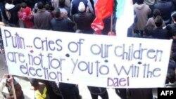 """Участники антиправительственной демонстрации на юге Сирии несут плакат с критикой Владимира Путина. Текст возможно перевести как """"Путин. Наши дети плачут не для того, чтобы ты победил на выборах"""""""