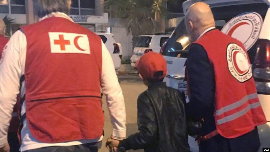 Në këtë fotografi, Alvin Berisha shoqërohet më 6 nëntor për në aeroëportin e Damaskut nga zyrtarë të Kryqit të Kuq dhe Gjysmëhënës së Kuqe.