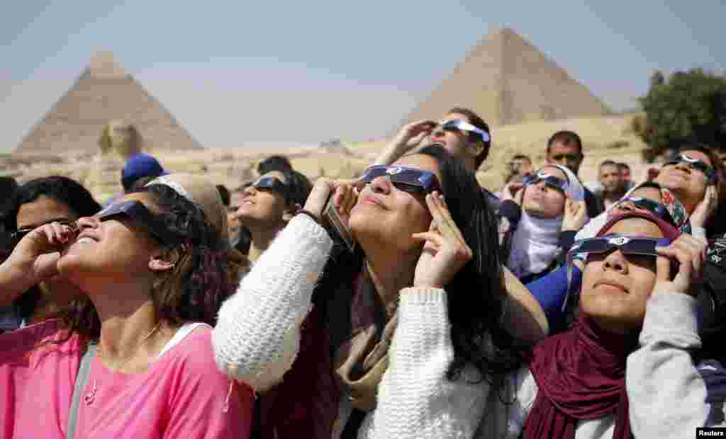 People look up to view a partial solar eclipse around the Giza Pyramids, on the outskirts of Cairo, Egypt. The total eclipse of the sun was only visable in the Faroe Islands and the Norwegian archipelago of Svalbard in the Arctic Ocean.