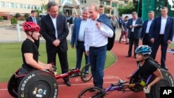 FILE - Russian President Vladimir Putin, center, speaks with athletes of the Russian Paralympic cycling team as he visits a sports training center in Sochi, the Black Sea resort that hosted this year's Winter Olympics, Russia, Oct. 23, 2014.