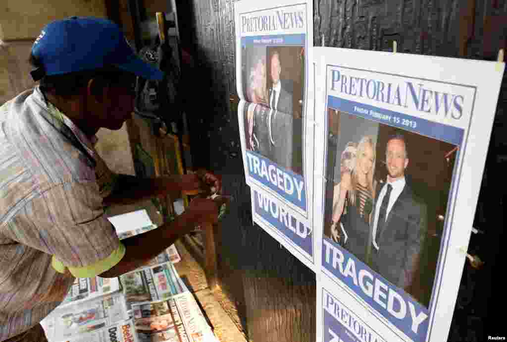 A newspaper vendor sets up his stall outside court ahead of Pistorius' court appearance in Pretoria, February 15, 2013.