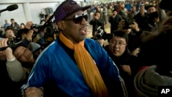FILE - Former NBA basketball player Dennis Rodman is followed by journalists as he arrives at the Capital International Airport in Beijing from Pyongyang.