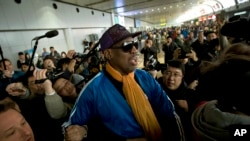 Former NBA basketball player Dennis Rodman is followed by journalists as he arrives at the Capital International Airport in Beijing from Pyongyang, Monday, Jan. 13, 2014.