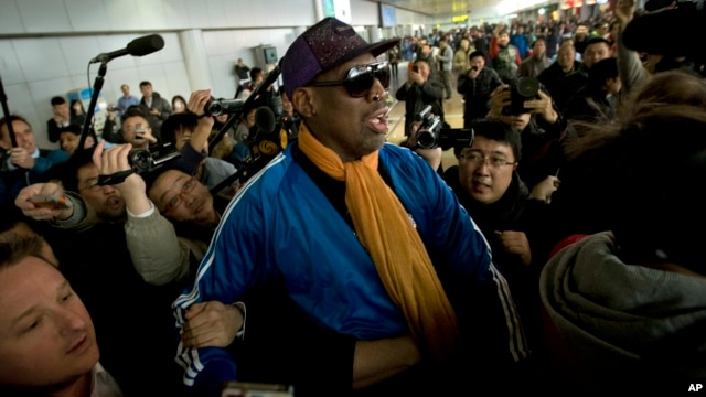Former NBA basketball player Dennis Rodman is followed by journalists as he arrives at the Capital International Airport in Beijing from Pyongyang, Jan. 13, 2014.