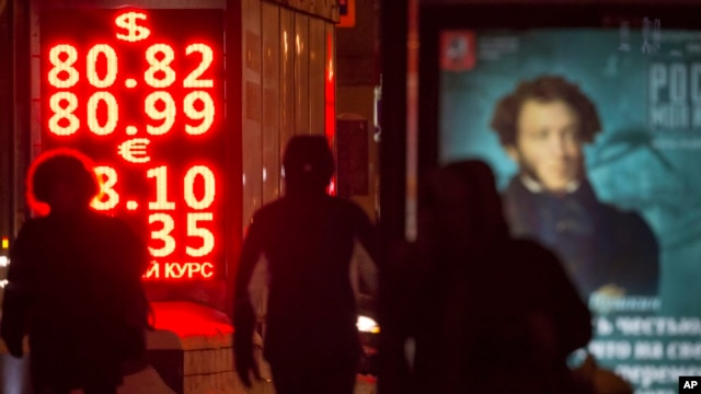 People walk past a currency exchange display board showing the value of the Russian ruble against the U.S. dollar and the euro, in Moscow, Russia, Jan. 20, 2016.