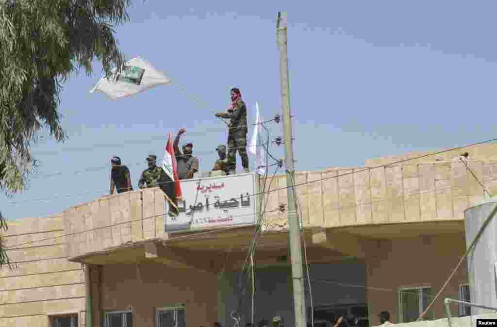 Triumphant Iraqi Shiite militia fighters celebrate breaking a long siege of Amerli by Islamic State militants, Sept. 2, 2014.