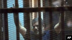 លោកប្រធានាធិបតី Mohammed Morsi ដែលត្រូវគេបណ្តេញពីតំណែងរបស់អេហ្ស៊ីបលើកដៃរបស់ឡើង ខណៈដែលគាត់អង្គុយនៅពីក្រោយកញ្ចក់ក្នុងសនវាការក្នុងប្រទេសអេហ៊្សីប កាលពីសៅរ៍ ទី១៦ ខែឧសភា ឆ្នាំ២០១៥។