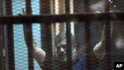 Presiden Mesir terguling, Mohammed Morsi di balik kaca di akademi polisi nasional di pinggiran timur Kairo, Mesir, Sabtu, 16 Mei 2015. Pengadilan Mesir menetapkan keputusan mati atas Presiden Mohammed Morsi. (AP Photo/Ahmed Omar)