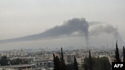 Khói bốc lên sau các vụ pháo kích của quân đội chính phủ Syria vào thành phố Homs