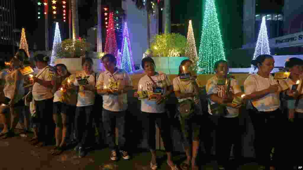 Une foule allume des bougies près des messages et des fleurs déposés à l'extérieur de l'ambassade française, dans le quartier financier de la ville de Makati, Philippines,16 novembre 2015.