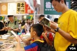 有家長帶同年小孩參觀書展,閱讀有關中國語文及粵語的書籍(美國之音湯惠芸)