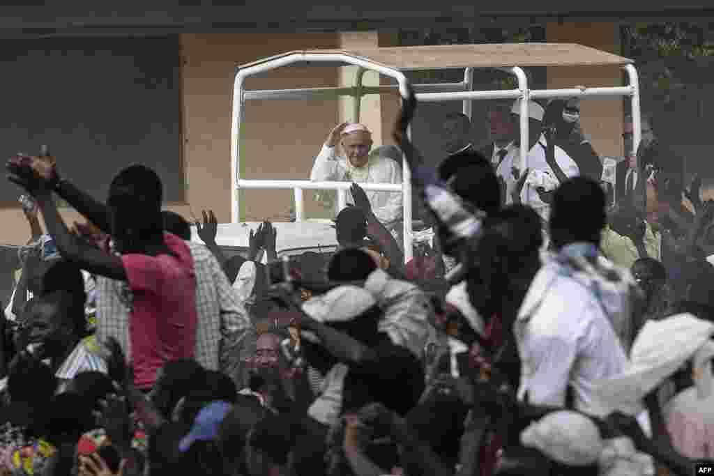 Pope Francis waves as he visits the Koudoukou school, to meet people from the Muslim community, after leaving the Central Mosque in the PK5 neighborhood in Bangui, Central African Republic.