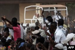 Pope Francis (C) waves as he visits the Koudoukou school, to meet people from the muslim community, after leaving the Central Mosque in the PK5 neighborhood in Bangui, Central African Republic, Nov. 30, 2015.