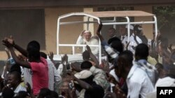 Pope Francis (C) waves as he visits the Koudoukou school, to meet people from the muslim community, after leaving the Central Mosque in the PK5 neighborhood on November 30, 2015 in Bangui.