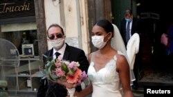 В Італії одружена пара у масках на церемонії лише зі свідками і без гостей, оскільки зібрання заборонені через карантин. Неаполь 20 березня 2020 р.