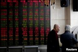 2019年1月18日,在北京一家经纪公司,投资者在显示股票价格的电子板附近聊天。由于北京与华盛顿的关税战谈判可能取得进展,中国股市在这一天上涨。