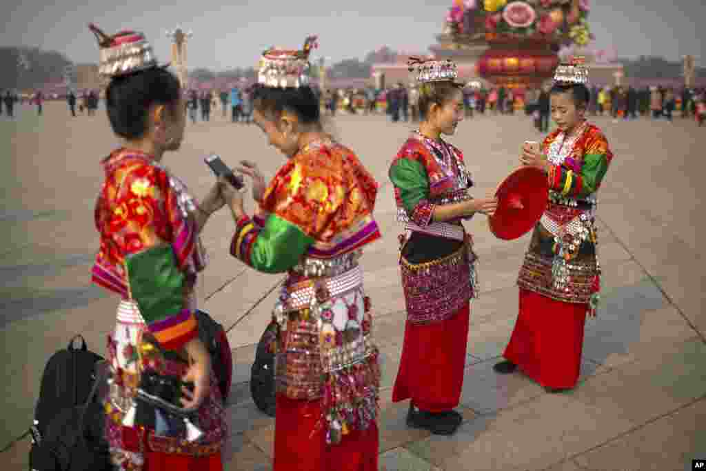 Women in ethnic minority dress look at their smartphones as they stand on Tiananmen Square in Beijing. U.S. President Donald Trump will visit China's capital on a on a three-day state visit beginning on Wednesday.