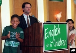 Jose Antonio Gonzalez, 10, left, cheers with other children as Proposition 227 writer Ron Unz addresses the media and supporters of the proposal to end bilingual education in the state, in Los Angeles Tuesday, June 2, 1998.