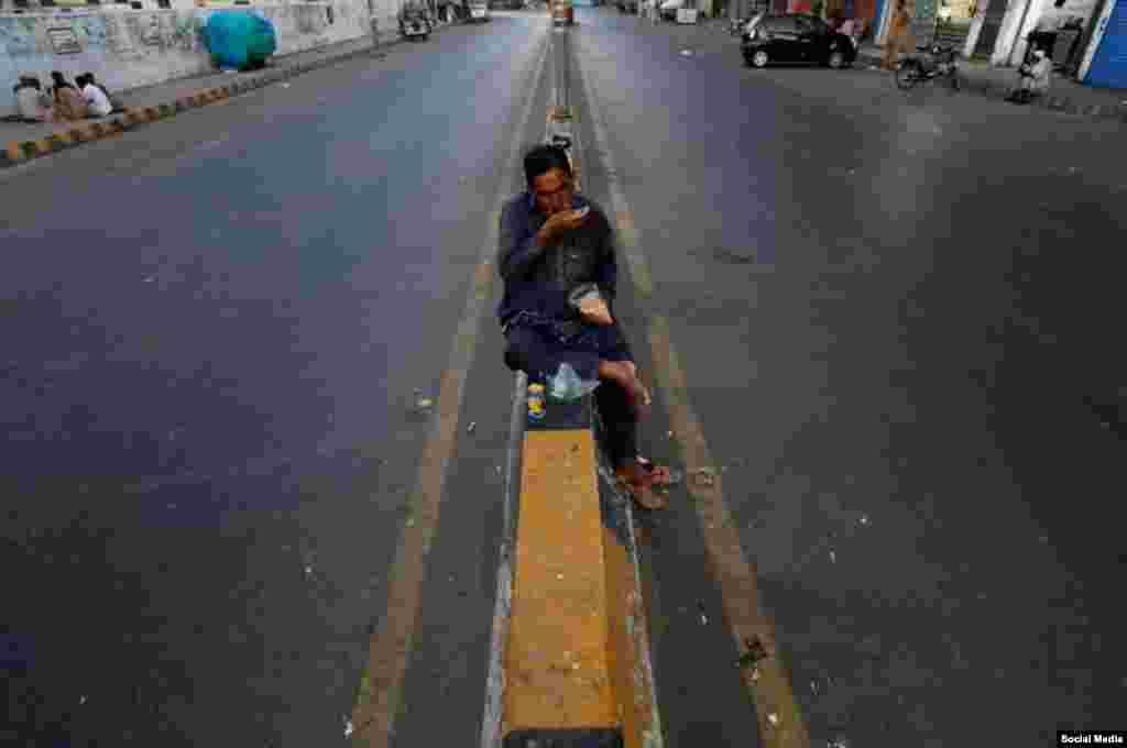 یک کارگر روزمزد در شهر کراچی پاکستان روزهٔ خود را افطار میکند.