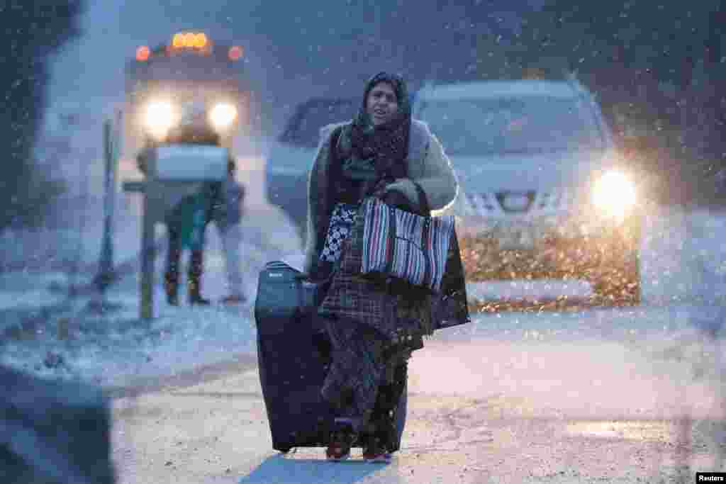 A woman walks toward the border to cross the U.S.-Canada border into Hemmingford, Quebec, Canada, after arriving in a taxi with a group that claimed to be from Syria.