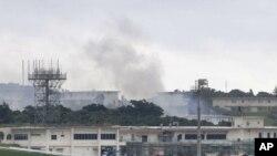 "Asap kebakaran mengepul dari gedung yang disebut ""18th Wing Hazardous Materials Pharmacy"" di Pangkalan Udara Kadena, pulau Okinawa, Jepang, Senin pagi, 22 Juni 2020. (Foto: Kyodo News via AP)"