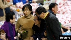 The family member of a missing passenger who was on South Korean ferry Sewol, which sank in the sea off Jindo, is helped as she cries while waiting for news from the rescue team, at a gym in Jindo, Apr. 18, 2014.