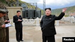 North Korean leader Kim Jong Un (R) gives field guidance during a visit to the construction site of the Paektusan Hero Youth Power Station near completion in this undated photo released by North Korea's Korean Central News Agency (KCNA) in Pyongyang, Sept