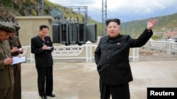 North Korean leader Kim Jong Un (R) gives field guidance during a visit to the construction site of the Paektusan Hero Youth Power Station near completion in this undated photo released by North Korea's Korean Central News Agency (KCNA) in Pyongyang, Sept. 14, 2015.