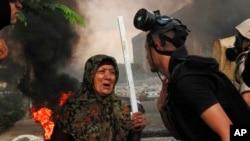 清理抗议营地的埃及安全部队成员跟手持木棍的妇人交谈
