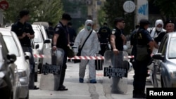 Riot police stand guard as forensic experts in white suits search for evidence on a street behind the headquarters of the co-ruling Socialist PASOK party in Athens, May 25, 2014.