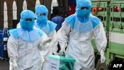 ရန္ကုန္ၿမိဳ႕ရွိ Quarantine စင္တာတခုမွာ ကိုဗစ္သံသယလူနာေတြရဲ႕ ၾကိဳတင္မဲေတြကို လာေရာက္ ေကာက္ခံတဲ့ PPE ဝတ္စံုဝတ္ မဲရံုဝန္ထမ္းတခ်ိဳ႕။ (ႏိုဝင္ဘာ ၀၆၊ ၂၀၂၀)