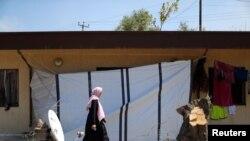 Une femme déplacée libyenne, qui a fui sa maison en raison des combats entre les forces orientales commandées par Khalifa Haftar et le GNA, marche dans un complexe industriel qui lui sert d'abri, à Tripoli, en Libye, le 16 avril 2019. REUTERS / Ahmed Jadallah