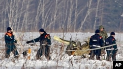 Personnel work at the scene of the AN-148 plane crash near Stepanovskoye, about 40 kilometers (25 miles) from the Domodedovo airport, Russia, Feb. 12, 2018. The plane carrying 71 people crashed Sunday near Moscow, killing everyone aboard.