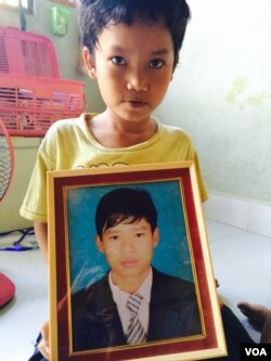Pheng Panha, who lost his older brother one year ago, shown here with his sibling's portrait at home in Phnom Penh's Dangko district.
