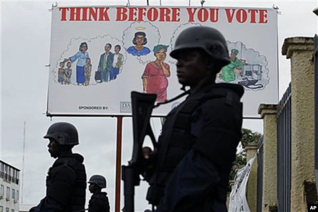 FILE - Liberian police equipped with riot gear stand guard outside the headquarters of the National Elections Commission in Monrovia, Liberia, Oct. 13, 2011.