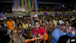 A child plays a toy guitar during a rally ahead of a general election in Bangkok, March 22, 2019. The nation's first general election since the military seized power in a 2014 coup is scheduled to be held March 24.
