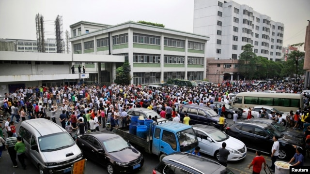 FILE - Workers protest during a strike as police stand guard at the factory area of Yue Yuen Industrial, in Dongguan, Guangdong province, April 18, 2014.