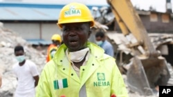 FILE- Ibrahim Farinloye, spokesman for the Nigerian Emergency Management Agency, speaks on the rubble of a collapsed building belonging to the Synagogue Church of All Nations in Lagos, Nigeria, Sept. 17, 2014.