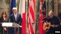 Mayor Paris Anne Hidalgo dan Menlu AS John Kerry mendengarkan lagu yang dibawakan oleh James Taylor di Balai Kota Paris dalam rangka mengenang korban teror di Paris (16/1) (Foto: Pam Dockins/VOA)